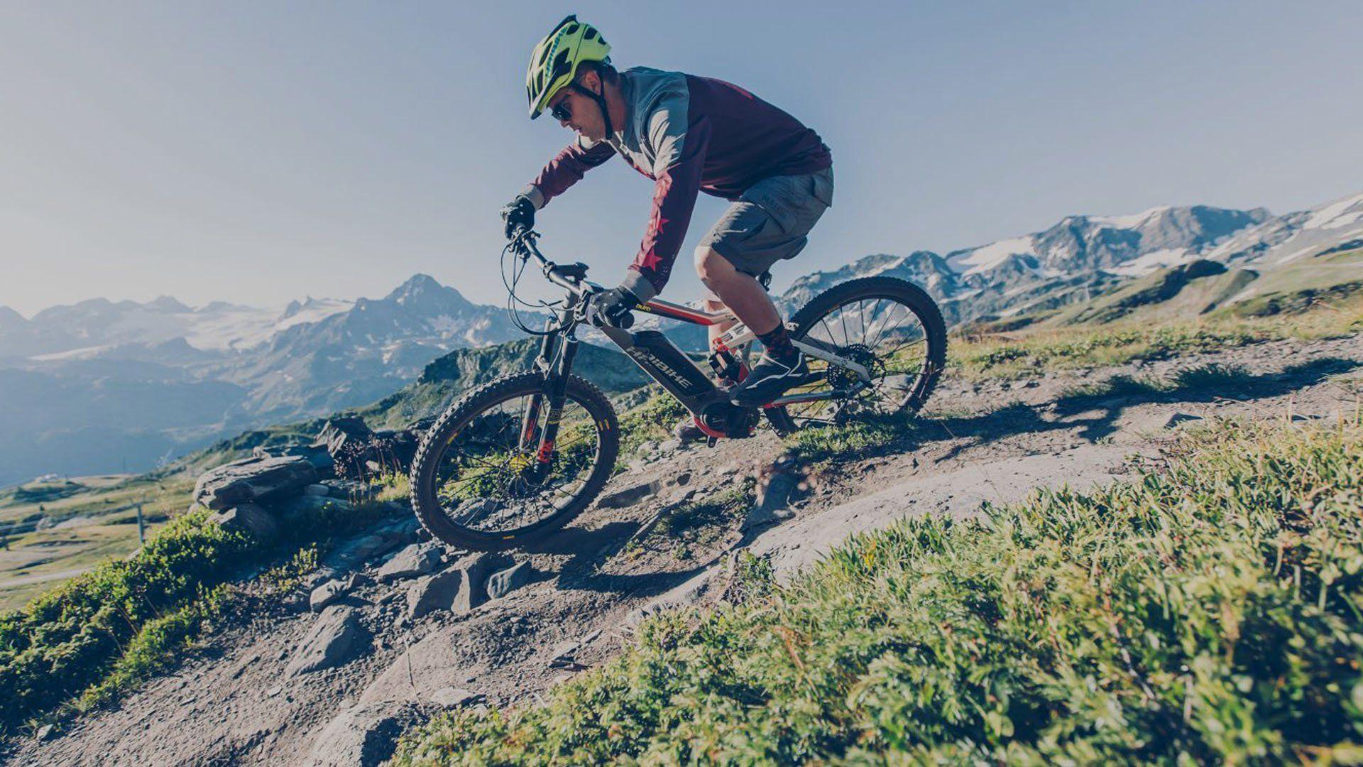 Ciclista in mountai bike effettua una curva in discesa in montagna ad Alleghe